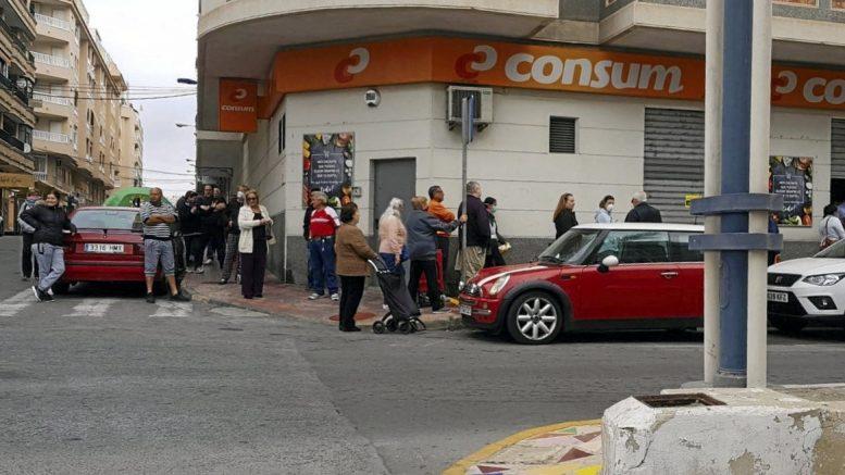 Ihmiset jonottavat Torreviejassa kauppaan, osa pitää välimatkaa toisiinsa.