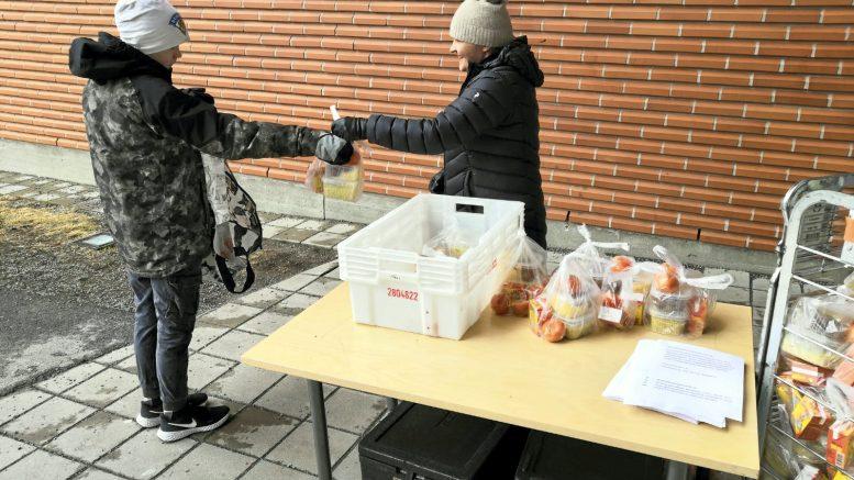 Väinö Vartiainen (vasemmalla) kävi noutamassa omat ja siskonsa ruoka-annokset Jäälin koululta. Hänen perheensä on ottanut ruokajakelun vastaan hyvillä mielin, sillä se helpottaa kummasti arkea. (Kuva: Ilpo Vartiainen)