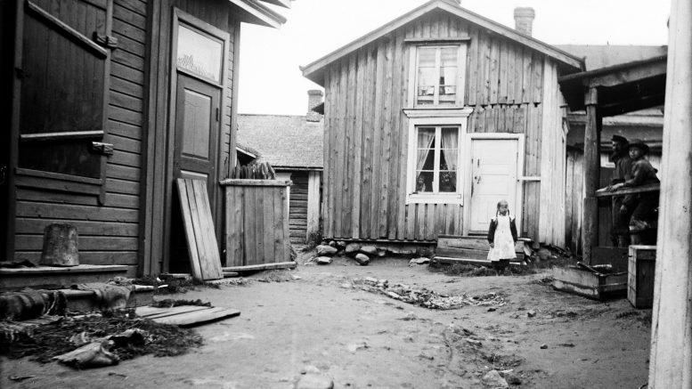 Tyttö seisoo Nuotanperän poikkikadulla Iin kirkonkylässä. Kuva on vuodelta 1913. Kuva: Samuli Paulaharju, Museovirasto.