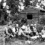 """Iin Brusilan talon väki kahvitauolla heinäntekoaikaan vuonna 1944. Kuva otettu talon lähellä sijainneen niityn laidalla. Henkilöt vasemmalta: inkeriläismies, joka tuli sodan alkuaikoina Iihin ja joutui perheineen palaamaan sodan päätyttyä Neuvostoliittoon, seuraavana Heikki Kurkela, edessä selin Eeva Kurkela (edellisen tytär), kaksi sotasairaalan miestä, """"setä-Matti"""", Heikki Kurkelan pojan vaimo Anni Kurkela, talon apulainen Lamminparras, neuvostoliittolainen sotavanki sekä suomalainen sotilas läheisestä sotasairaalasta. Kuva: Museovirasto, kuva kopioitu alkuperäisestä nitraattinegatiivista."""
