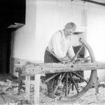 Hannusvaari tekee puista vaununpyörää vuonna 1913. Kuva: Museovirasto, kansantieteen kuvakokoelma, Samuli Paulaharjun kokoelma.