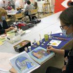 Ikoneihin maalataan useita maalaus- ja värikerroksia ja yksityiskohdat ovat pikkutarkkoja. Kristiina Karivuori (oik.) maalaamassa ikonia aiheeksi valitsemansa vanhan mallin mukaan. Pöydän toisella puolella Airi Vainionpää.