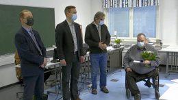Kunnanjohtaja Ari Alatossava (vasemmalla), kunnanhallituksen puheenjohtaja Johannes Tuomela ja kunnanvaltuuston puheenjohtaja Teijo Liedes luovuttivat ansiomerkin ja kukat Kehukselle maanantaina. (Kuvankaappaus livelähetyksestä)