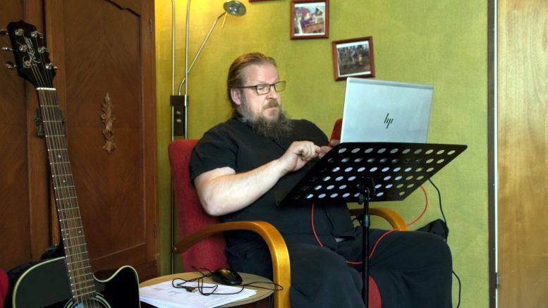 Vuorovaikutustaitoja OSAO:lla opettava Juha-Pekka Sillanpää pitää etätyöpäivinä kotikonttoria olohuoneen nurkassa. Tietokonepöydäksi on näppärästi taipunut nuottiteline.