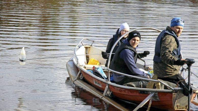 Ninni Laukkanen ottamassa vesinäytettä pulloon, vierellä Markus Saari ja tutkijoita veneellä kuljettanut Tomi Hoikka. Vesinäytteistä tutkitaan Vahtolanlahden valuma-aluetta kuormittavia tekijöitä.