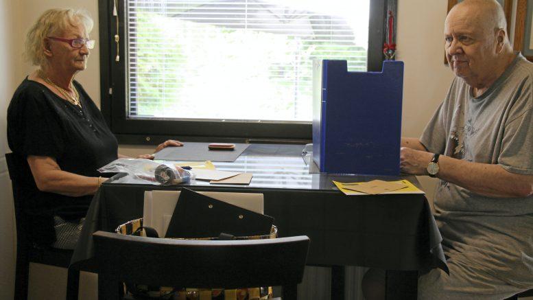Veli-Matti Kansanaho äänestää pöydälle pystytetyn sermin takana. Puoliso odottaa vuoroaan.
