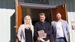 """Kerholassa lapsena asunut Sakari Kuparinen (keskellä) toi paikan uusille omistajille Hanna ja Pekka Qvistille tuliaisena harvinaisen kirjan """"Pojat kansan urhokkaan"""", joka kuului aikoinaan Kerholan kirjaston kokoelmiin."""