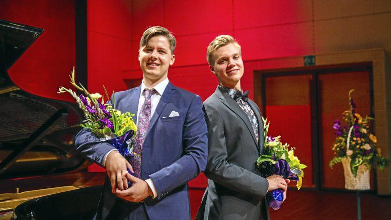 Johan Krogius (vas.) ja Jere Hölttä olivat kilpakumppaneita Timo Mustakallio -laulukisassa. Kilpailu kuitenkin tuntui enemmän ystävien väliseltä sparraamiselta, koska kilpailijat tunsivat toisensa jo ennen kisaa.