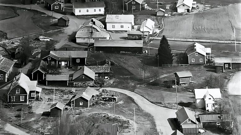 """Halosenniemen kylä keväällä 1960 ilmasta käsin. Kuvassa näkyvät mm. Runtin talo ulkorakennuksineen (yläreunassa pitkähkö vaalea talo), oikealla puolella siitä Matti Metsikön talo navettoineen ja alapuolella vanha Haukiputaan Osuuskauppa. Vastapäätä Oulun Osuuskauppa, alapuolella vanha Halosen talo, joka myös Åströmin talona tunnettiin. Vaalean mansardikattoisen talon pihaan (oik.) johtaa """"oikea tie"""", sillä kyseessä on autoilija K. Törmän talo, joka ajoi linja-autoa kylältä Haukiputaalle ja takaisin."""