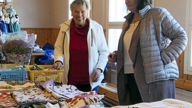 Eila Korva (vasemmalla) on tuttu näky Kuivaniemen nuorisoseuran myyjäisissä ja markkinoilla. Verhot, liinat ja monet muut tuotteet valmistuvat Korvan ompelukoneen tikatessa. Apulaisena hyöri Ulla Hirvaskoski.