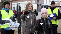 Kotikoulutoimikunnan jäsenet Marjo Raappana (vas.) ja Jutta Arolaakso huomasivat, että koululaiset ilahtuivat heijastimista. Jenna ja Miia Raappanalla on pimeään aikaan useita heijastimia.