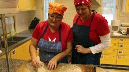 Sirkka-Liisa Turtinen ja Maritta Päkkilä pistelivät kohonneita leipiä ennen paistamista.